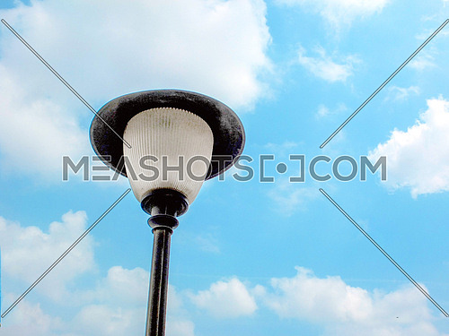 A lamp post towards the sky and clouds