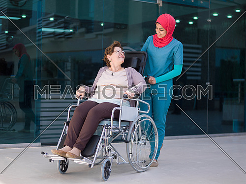 older sick woman in wheelchair with young nurse at  hospital