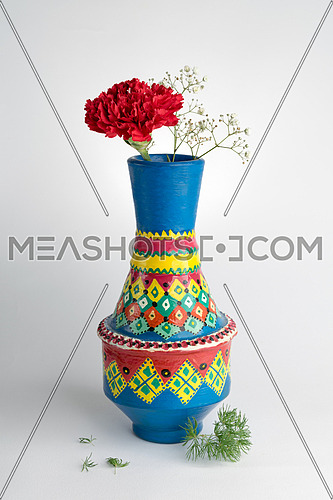 Still life composition of colorful pottery vase with a red flower on white background