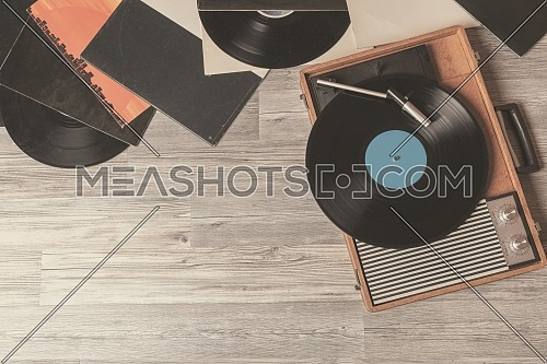 Vintage Gramophone with a vinyl record on gray wooden table, top view and copy space