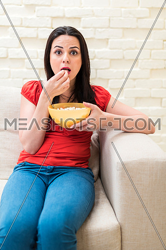 young lady eating popcorn with exciting impression while sitting on sofa