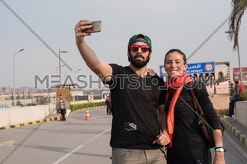 Young middle eastern attractive couple enjoying a holiday photographing themselves