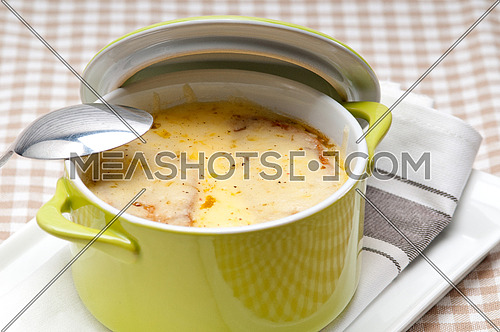 onion soup on clay pot with melted cheese and bread on top