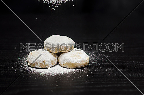 3 kahks on a black table with white sugar sprinkled on the kahk while the rest of sugar is being sprinkled and flying on the top of the frame