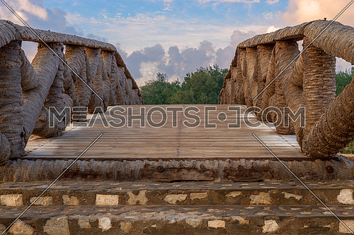 Wooden bridge made of palm trunks leading to trees with partly cloudy sky in sunrise time at Montaza public park in summer time, Alexandria, Egypt