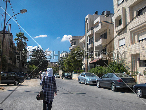 A girl walking in the street surrounded with buildings and cars