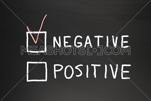 Negative and positive written on a black slate with chalk. In red marked negative box, conceptual image