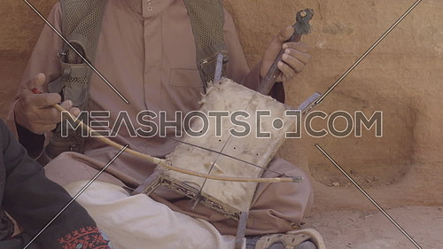 View of man playing the Rababa on canyon trail into Petra