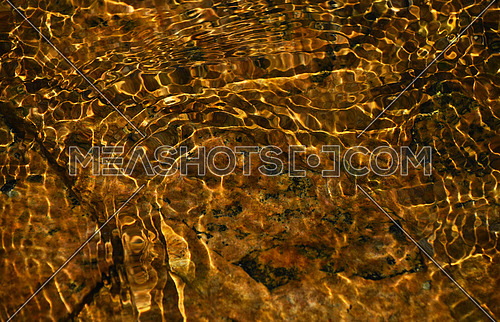 Running water golden color stream deflection flowing over brown stones texture background