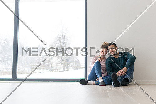 happy young couple sitting near window at home on cold winter day