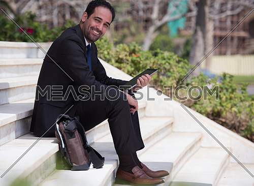 Business executive sitting on the steps of a corporate building working with his tablet
