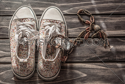 Used  sneakers and necklace on a wooden floor.
