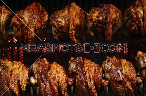 Several traditional Bavarian German roasted pork knuckles slowly cooked at rotating broiling rack grill spit, close up, low angle side view