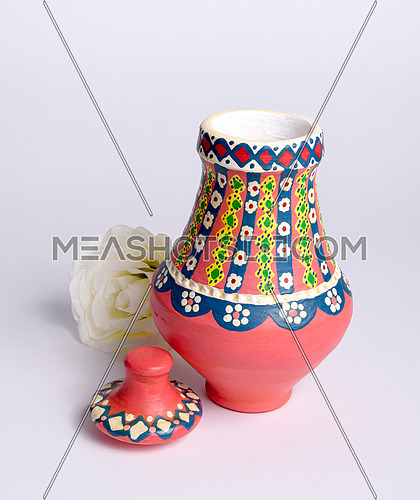 Pink Egyptian decorated colorful pottery vase (arabic: Kolla) made of clay and white flower on white background