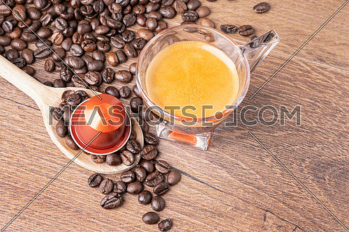 Cup of coffee with coffee capsule on wooden spoon, roasted coffee beans on wooden background,top view.