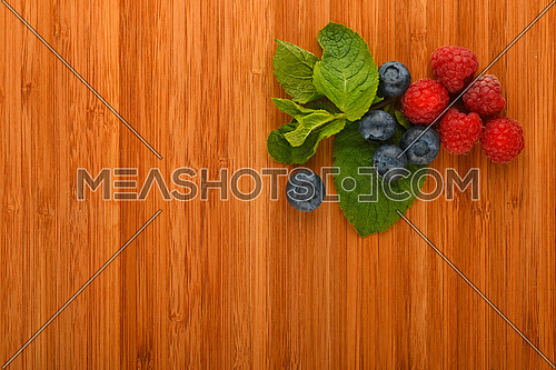 Taste of summer - cutting board with mellow blueberries, raspberries and mint leaves – add your text