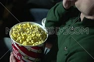 High angel for young man eating popcorn at movie theatre.