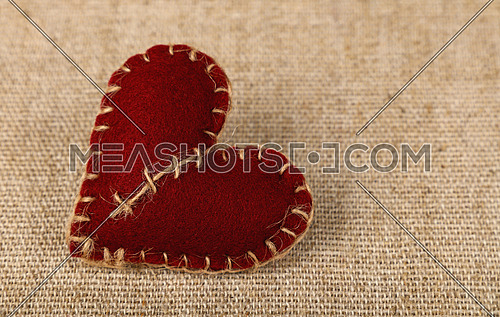Valentine Day template, one handmade brown felt craft stitched toy heart on linen canvas, close up, high angle view