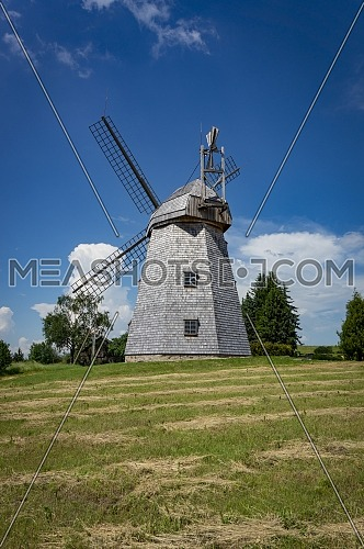 Old windmill in grassland in a country landscape with woodland trees under a cloudy blue sky in a scenic landscape
