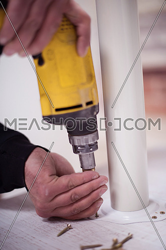 repairman working with drilling machine and assambling  furniture