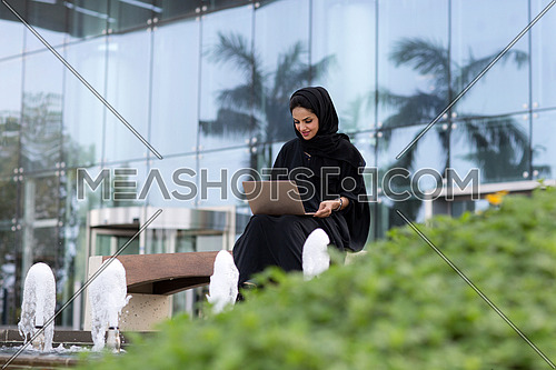 Saudi lady setting down, working on laptop, wearing black abaya in front of glass building and a small garden in background at day.