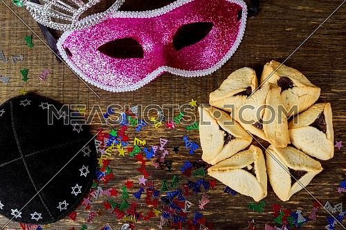 Jewish holiday Purim with carnival mask and homemade hamantaschen cookies, kippah flat lay