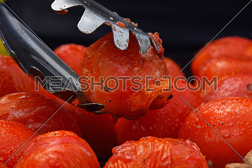BBQ small red tomatoes cooked on barbecue, tongs holding one tomato, picking it up from grill