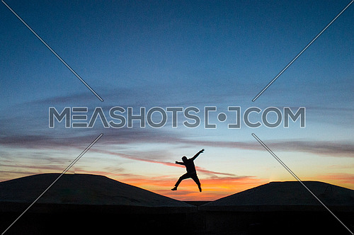 a young man silhouette jumping of joy on a sunset landscape background