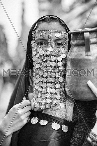 portrait of a young middle eastern woman in a traditional costume with gold coins over her face and a jug in her hands