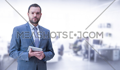 Portrait of young junior businessman using tablet in front of his big modern office