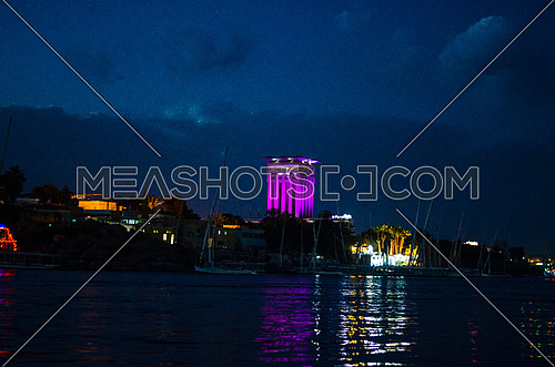 A view of Aswan city at night in front of the Nile river in Egypt