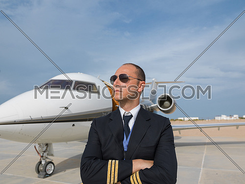 Portrait of a young middle eastern successful pilot with sunglasses in front of the a private airplane