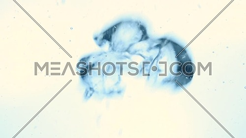 Extreme close up abstract background of cold blue air bubbles emerging underwater over warm white background, low angle side view, slow motion