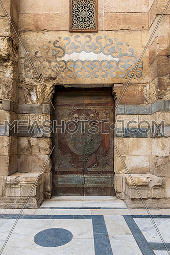 Wooden decorated copper plated door and stone bricks wall leading to Sultan Barquq mosque, Al-Moez Street, Old Cairo, Egypt