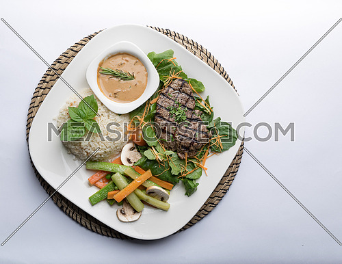 Thick cut beef filet steak served with rice, vegetables, mushroom, and gravy sauce on white porcelain dish