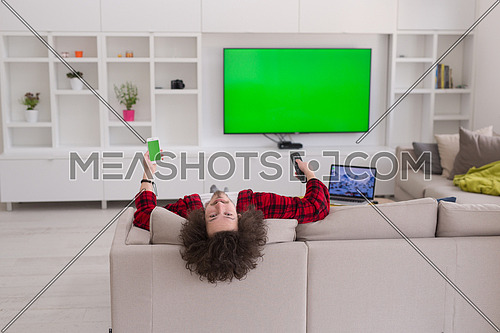 young handsome man in bathrobe enjoying free time watching television in his luxury home