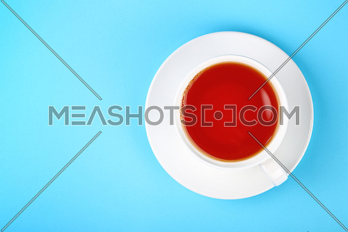 Close up one full white cup of black or red fruit infusion tea on saucer over pastel blue paper background, elevated top view, directly above