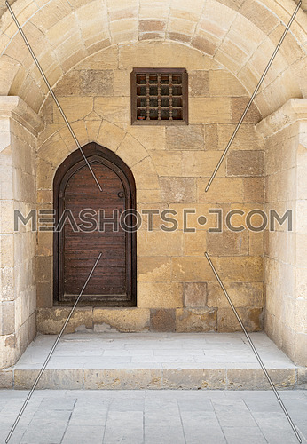 Wooden aged vaulted ornate in a recessed stone wall at caravansary (Wikala) of Bazaraa, Medieval Cairo, Egypt