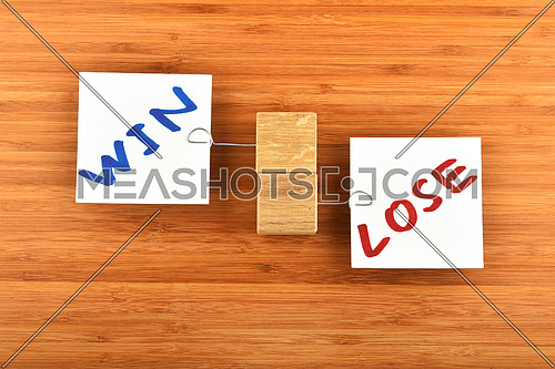 win lose, two white paper notes with wooden holders in different directions on wooden bamboo background for presentation