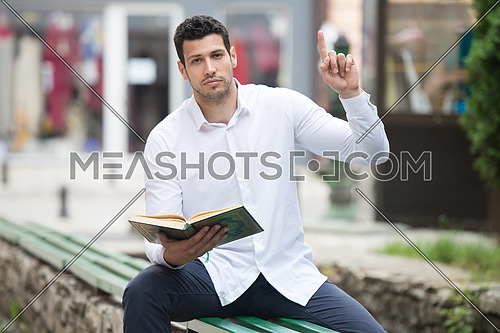 Adult Muslim Man Is Reading The Koran Outdoors