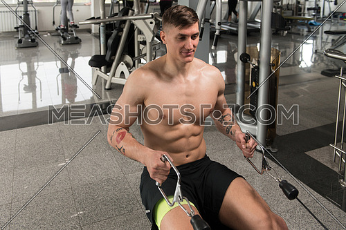 Young Man In The Gym Exercising On His Back On Machine With Cable In The Gym
