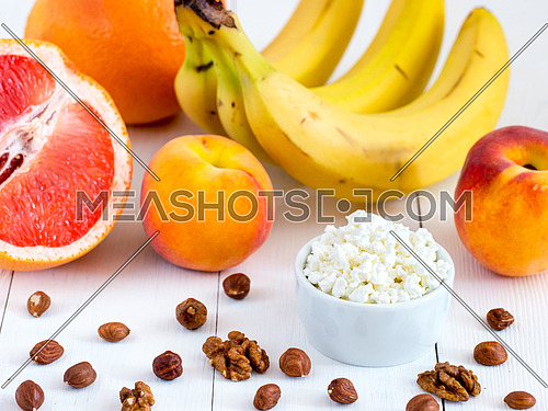Healthy breakfast: cottage cheese, fruits and nuts on white wooden background. Dieting, healthy lifestyle concept meal