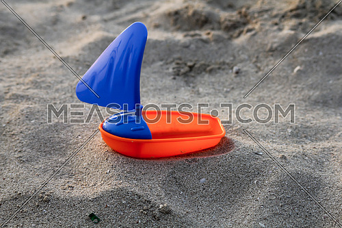 plastic toy boat in the sand