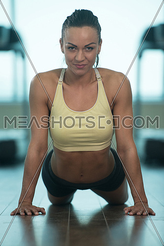 Muscular Woman Stretches At The Floor In A Gym And Flexing Muscles - Muscular Athletic Bodybuilder Fitness Model
