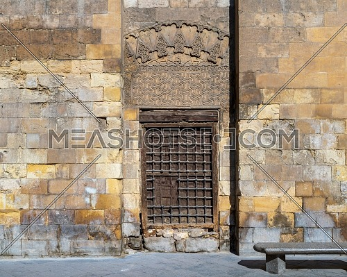 Grunge wooden window with decorated iron grid over stone bricks wall and marble garden bench, Moez Street, Cairo, Egypt
