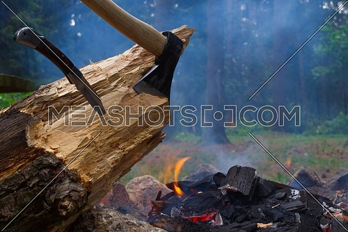 Camp fire in a forest with chopper and folding pocket knife lodged in a log of wood in the foreground in a healthy active lifestyle concept