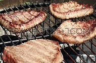 Grilled beef bbq steaks cooking roasting on outdoors fire flame barbecue grill, poured and dredged with spices and herbs, close up