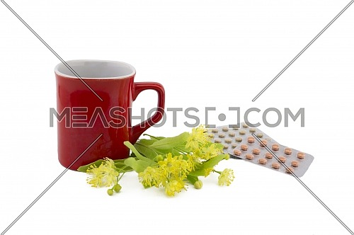 Red cup near freshly picked yellow linden flowers and pills in a blister over a white background, therapeutic or alternative healing concept