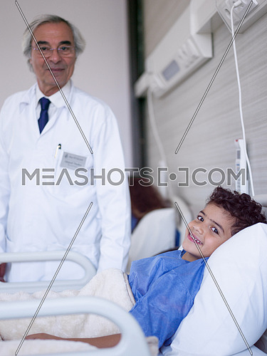 arabian mischievous and beauty kid get treatment by mature doctor in modern hospital
