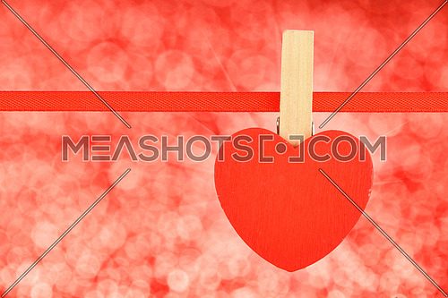 Red heart at ribbon over red glitter blur